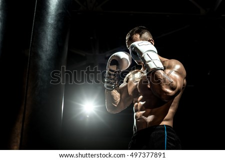 boxer in gym with boxing gloves, safeguard stand, black bacground, horizontal photo