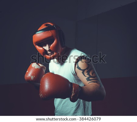 Boxer in helmet on a dark background, where the face is not visible. Male boxer in red helmet and gloves. Sports man boxing. Training. Fighter, warrior, fighting without rules.  Toned image. - stock photo