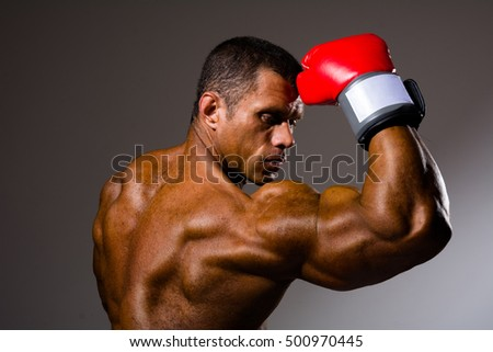 Boxer in rack ready for battle. Athletic man with boxing gloves on a gray background