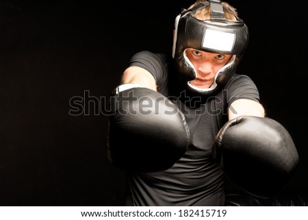 Boxer punching towards the camera with both of his gloved fists with a look of determination, on a dark background with copyspace - stock photo