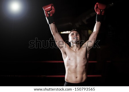 Boxer raising his arms and celebrating his recent victory in the ring.  - stock photo