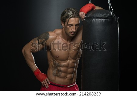 Boxer With Punch Bag In Action - A Man With A Tattoo In Red Boxing Gloves - Boxing On Black Background - The Concept Of A Healthy Lifestyle - The Idea For The Film About Boxing - stock photo