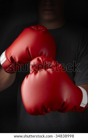 Boxer with red boxing gloves about to throw a punch - stock photo