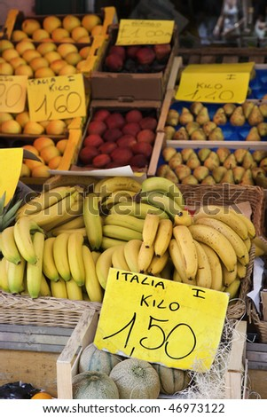 Boxes of bananas and other fruits at a market in Italy. Vertical shot. - stock photo