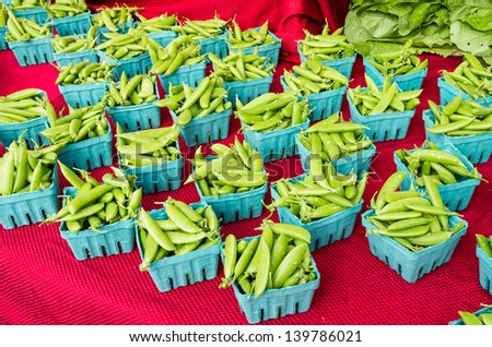 Boxes of freshly harvested peas on display at the farmers market - stock photo
