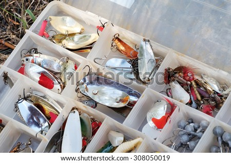 Boxes with a set of spinners for fishing. The fisherman's box for baits. - stock photo