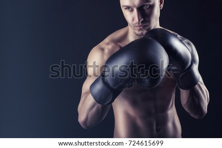 Boxing concept. Boxer with an aggressive look in boxing gloves before a fight against a black background