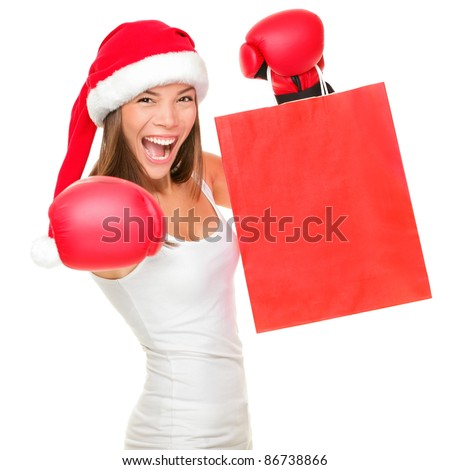 Boxing day shopping woman in Santa hat holding shopping bag with copy space. Energetic funny image of beautiful Caucasian / Asian female model isolated on white background. - stock photo