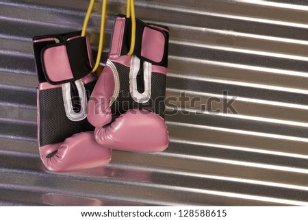 Boxing gear stored unused in the gym pink gloves against metal  - stock photo