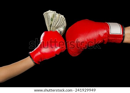 Boxing glove and a hand full of cash. - stock photo