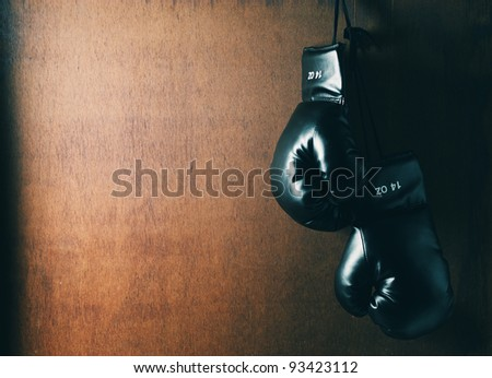 Boxing glove hanging on wooden grunge background - stock photo