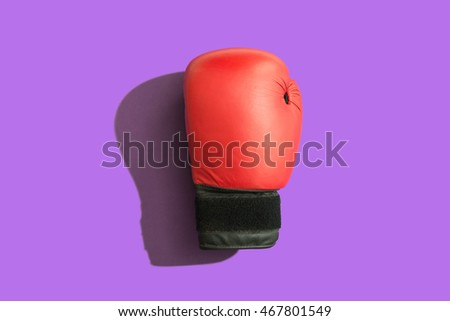 Boxing glove with shadow over a purple background