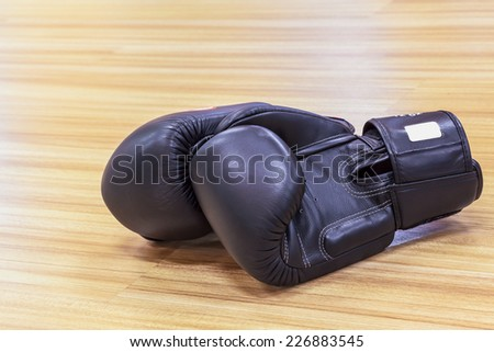Boxing gloves black color on wooden floor - stock photo