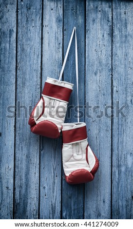 Boxing gloves hang on the old blue wooden wall from a nail - stock photo