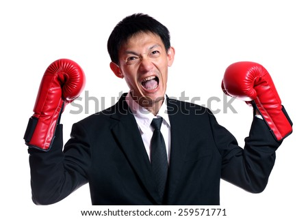 Boxing gloves man - concept showing aggressive female  flexing muscles wearing boxing gloves isolated on white background.Handsome young businessman with boxing gloves. Studio white background  - stock photo