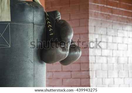 Boxing gloves on a punching bag in the gym against a brick wall