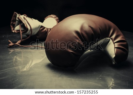 Boxing gloves on reflective surface - stock photo