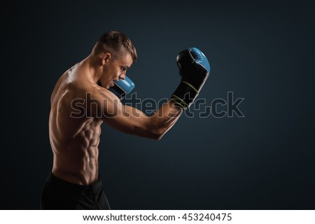 Boxing in studio. Strong boxer is protected - stock photo