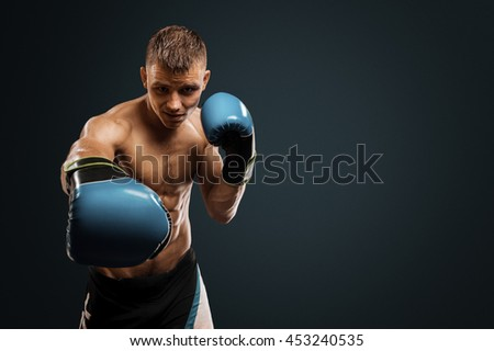 Boxing in studio.Strong boxer makes an impact on the camera - stock photo