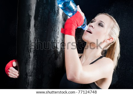 Boxing training woman drink water hold punching bag - stock photo