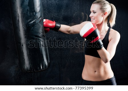 Boxing training woman with punching bag in gym wear gloves - stock photo
