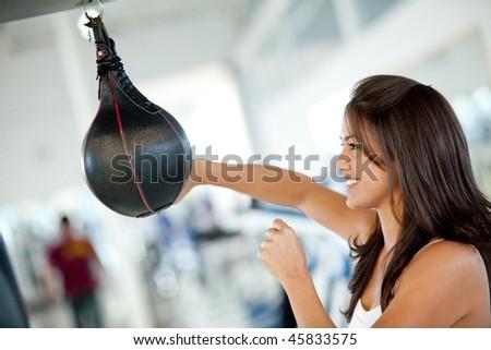 Boxing woman at the gym hitting a punching ball - stock photo