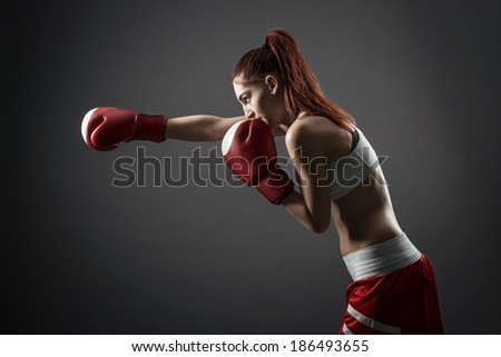 Boxing woman during exercise-gray background - stock photo
