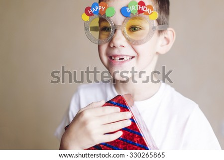 boy accepts congratulations on the birthday. cheerful boy holding a gift and receiving congratulations from friends and family birthday - stock photo