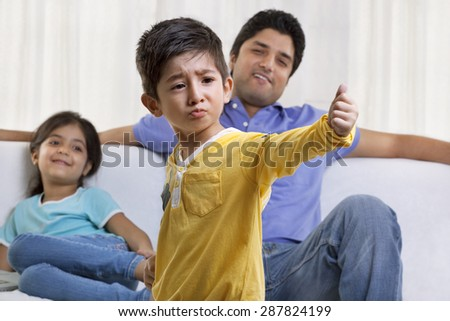 Boy acting in front of father and sister - stock photo
