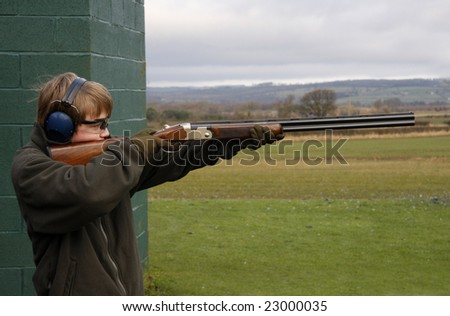 Boy aiming at the clay pigeon - stock photo