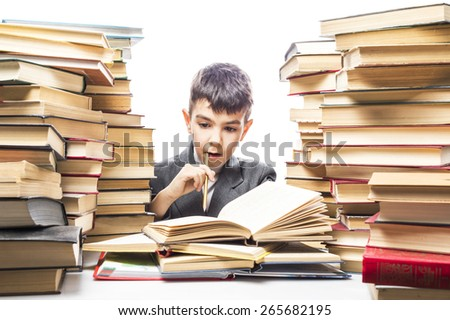 boy among the books reads biting a pencil - stock photo