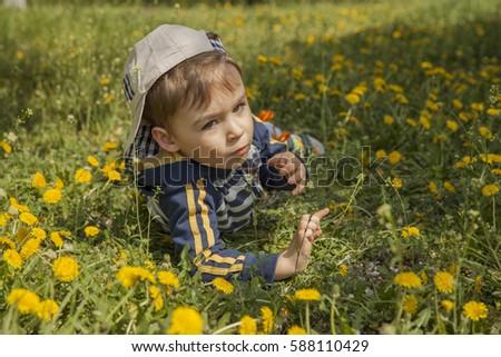 boy among yellow flowers in spring park