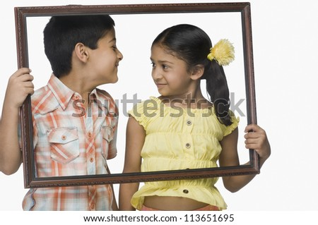 Boy and a girl holding an empty picture frame