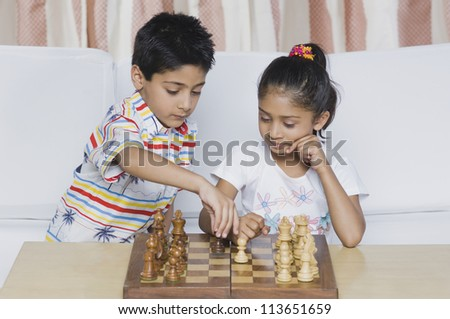 Boy and a girl playing chess - stock photo