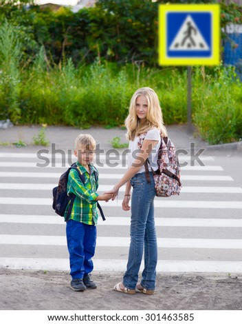 boy and a girl standing near a pedestrian crossing - stock photo