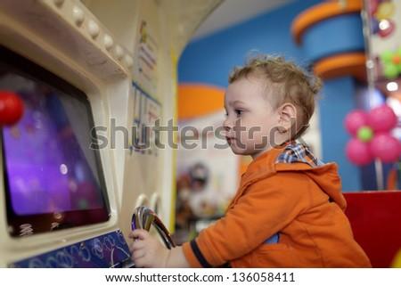 Boy and amusement machine at indoor playground - stock photo
