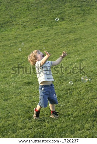 boy and bubbles on a grass - stock photo