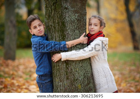 boy and girl among the leaves in autumn park