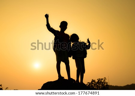 Boy and girl are climbing the hill during sun set. - stock photo