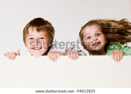 Boy and girl are holding empty board - stock photo