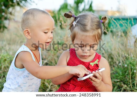 boy and girl are playing phone outdoors - stock photo