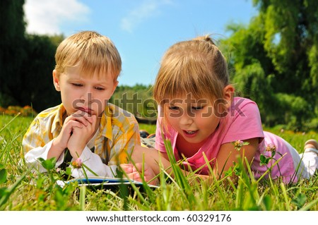 Boy and girl are reading a book outdoor