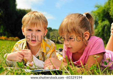 Boy and girl are reading a book outdoor - stock photo