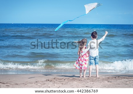 Boy and girl at the beach with a kite. Freedom, carefree childhood and hope. Brother and sister together. - stock photo