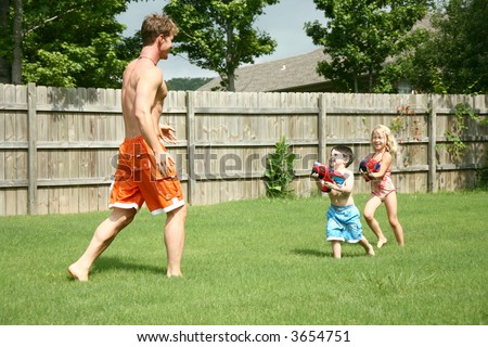 Boy and girl chase dad with waterguns. - stock photo