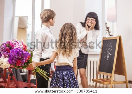 Boy and girl children give flowers as a school teacher in teacher's day. The day of knowledge, education, appreciation, generation. - stock photo