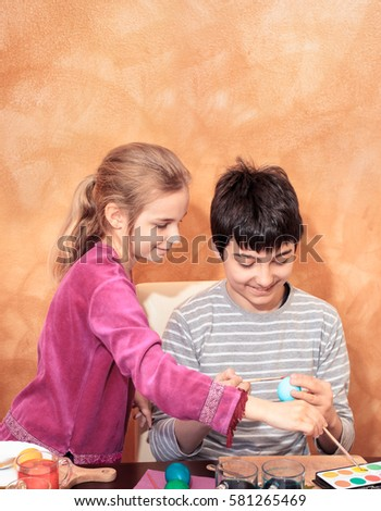Boy and girl decorating easter eggs at the table at home. Orange brushed wall as space for text in the background