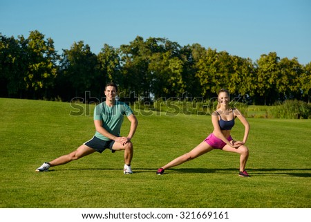 Boy and girl doing gymnastics on the nature. Sports trainers show the exercises. Sports on the nature.