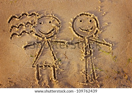 Boy and girl drawn in the sand/Sea background with a sand/Valentines day background - stock photo