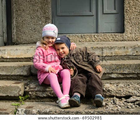 Boy and girl embrace on a staircase - stock photo